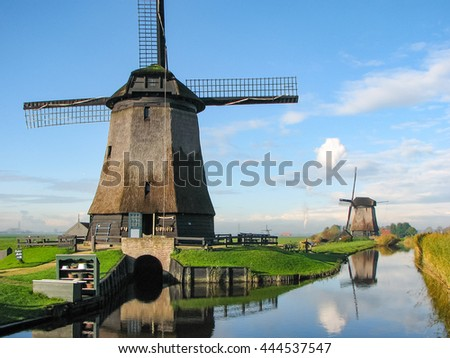 Windmills by a blue canal in the Netherlands in summer - stock photo