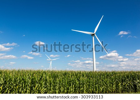 Windmills for renewable clean energy - The structures sprout from corn fields in the Midwest. Puffy white clouds dot the blue sky. - stock photo