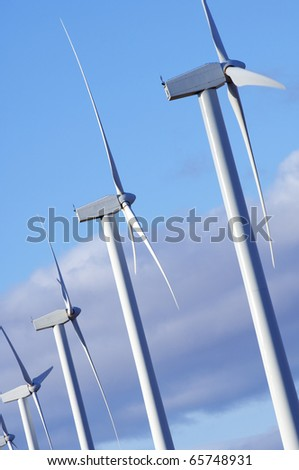 windmills group with blue and cloudy sky - stock photo