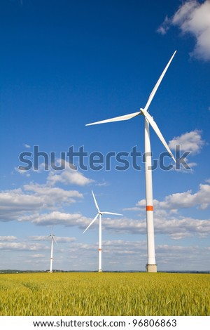 Windmills in a field of crop with blue sunny sky - stock photo