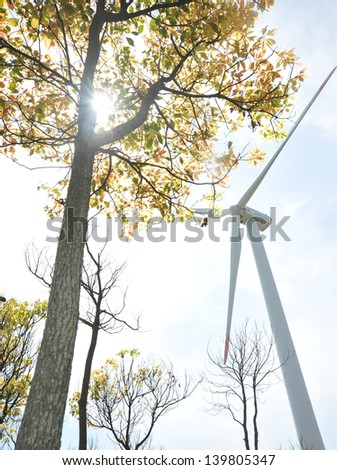 Windmills in a field of forest with sunny sky - stock photo