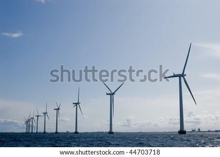 Windmills in a row with clear sky - stock photo