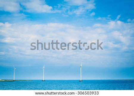 Windmills on a row in the blue ocean - stock photo