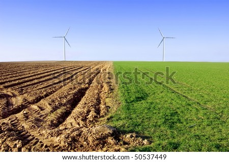 Windmills on the field conceptual image. Windmills on the plowed and green field. - stock photo