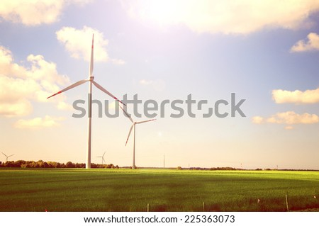 Windmills on the green field against sunshine sky at summer. Alternative energy - stock photo