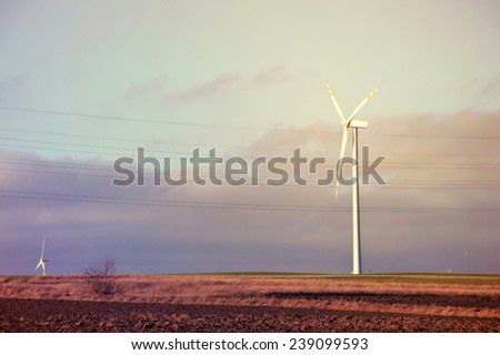 Windmills on the plowed field. Sunburst vintage picture. Alternative energy. - stock photo