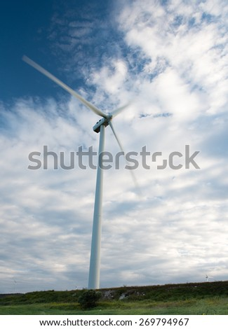 Windmills  power generators on a turbine farm generating electricity from wind on an idyllic landscape in Cyprus.  Concept of alternative energy.  - stock photo