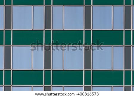Window. Abstract pattern of blue windows on green building. Facade window. Blue window. Window pattern. Building window. View of window. Modern window. Frame of window. Abstract window. Sunny window. - stock photo