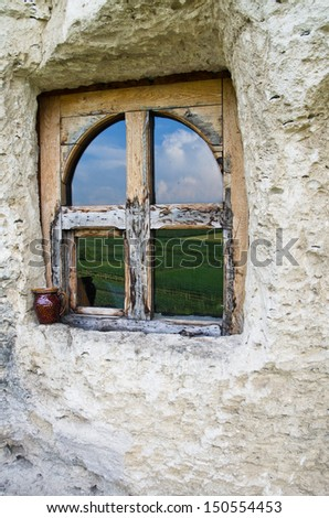Window cut into the stone reflecting the valey - stock photo