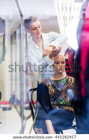 Window dresser working at shop promotion putting new fashion collection on mannequin - stock photo