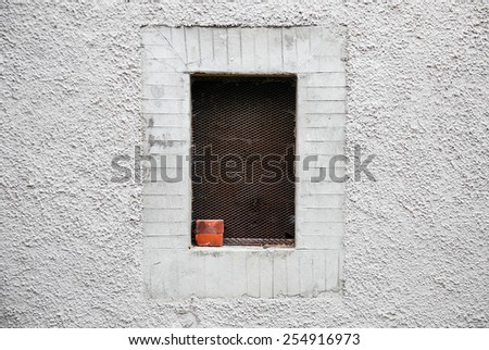 Window framed in whitewashed wall of alley in a village of Tuscany - stock photo