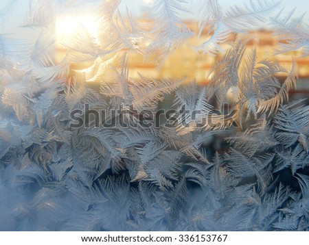 Window glass covered in frost in the afternoon sunlight reflected from another house. Blue sky, frost sparkling in the orange sunlight. Complicated patterns New Year and Christmas winter background. - stock photo