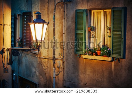 Window in an old house decorated with flower pots  at night  - stock photo