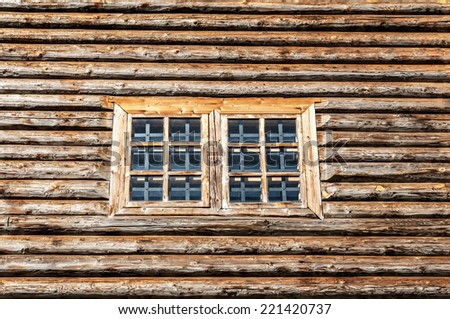 Window in the side wall of historic log cabin - stock photo
