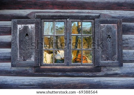 Window of a traditional Norwegian hut with beautiful reflection - stock photo