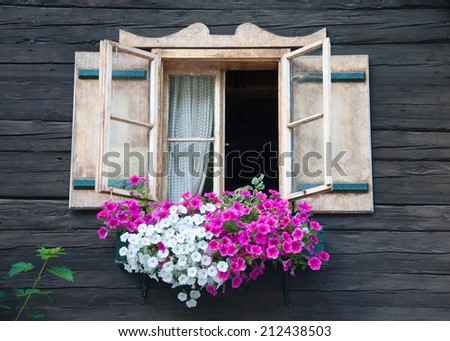 window of a wooden hut decorated with white and pink flowers - stock photo