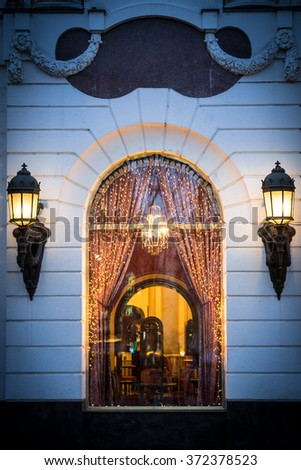 WIndow of cafe in Budapest, Hungary, Europe. Christmas decorations and lights. Two big street lamps on sides of window. Cozy and warm interior of restaurant. - stock photo