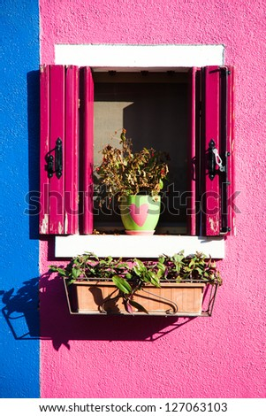 window on a colorful house wall in Burano, Venice - stock photo