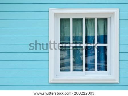 Window on blue wooden wall. - stock photo