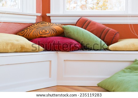 Window seat with colorful pillows. Close up bright sunny image. Warm, casual, inviting, fun interior space. Horizontal - stock photo