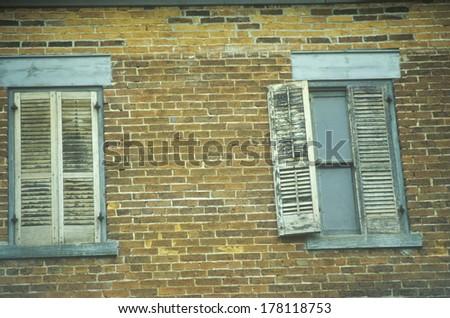 Window shutters on an abandoned brick hotel, PA - stock photo