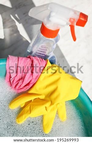 window washer set - rubber glove, wet duster, spray glass cleaner bottle, soap suds water in basin on windowsill - stock photo