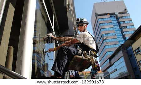 Window Washers on a Office Building. Industrial climbing - Facade Cleaning. - stock photo