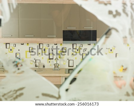 window washing with squeegee and detergent, with home kitchen in background - stock photo