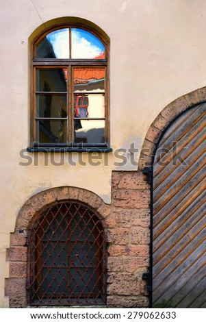 Window with a reflection of the sky and the roof with old gates and bars on the facade of a house in the old town of Riga - stock photo