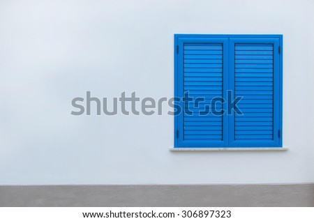 Window with blue shutters on a white wall. Window with closed shutters. Blue window in the wall of the house. - stock photo