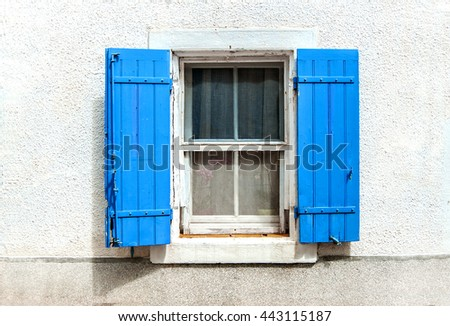 window with blue shutters on white wall background - stock photo