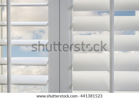 Window with blue sky and white cloud: white plantation shutter window for luxury interior window design, window with blue sky and white cloud in the background concept for summer day. sky sky sky sky  - stock photo