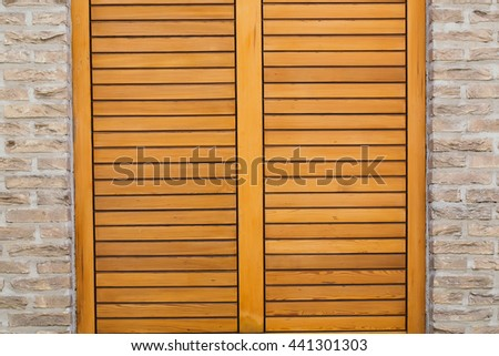 Window with bright brown horizontal wooden shutters in stone brick wall background - stock photo