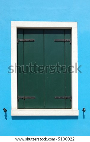 Window with closed green shutters, white outline, on a bright blue house in Burano Italy - stock photo