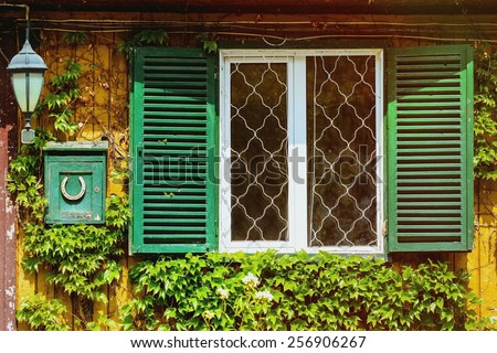 Window With Opened Shutters And Letterbox Near It - stock photo