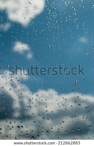 window with rain drops and a cloudy stormy sky outside - stock photo