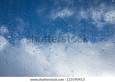 Window with raindops and blue sky - stock photo