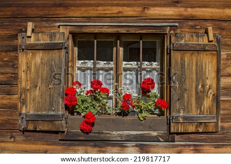 Window with shutters and flower decoration on old hut - stock photo