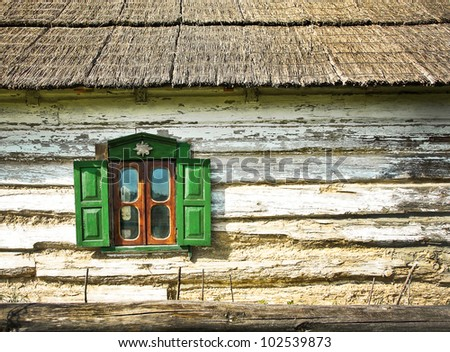 Window with shutters on the facade of an old wooden farmhouse. Country log house with a reed roof - traditional Ukrainian house in the village. Background with old rural chalet and window frame. - stock photo