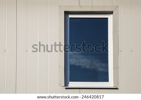 Window with sky reflection in light yellow color plastic siding panels wall - stock photo