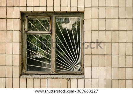 Window with steel bars on tile wall on sunny day - stock photo