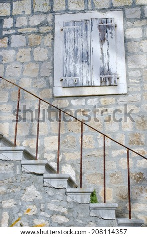 window with stone stairs in old stone house, Croatia - stock photo