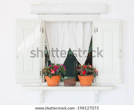 Window with white curtains and flowers in pots on the windowsill. - stock photo