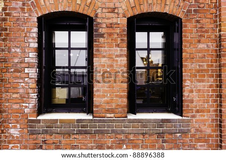 Windows in a red brick wall. - stock photo