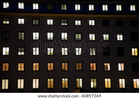 windows of a business house with light by night giving a structured impression, vienna - stock photo
