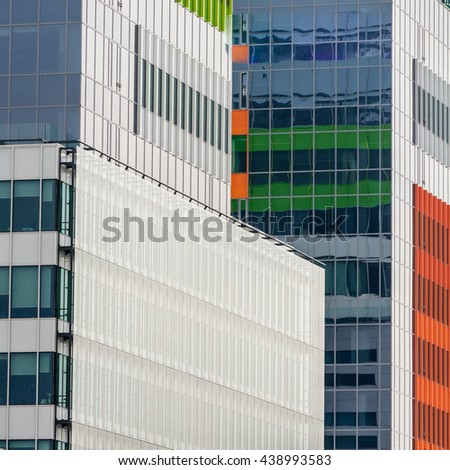 Windows of a modern business building exterior. Vertical image of abstract modern building background for design with colorful windows. - stock photo