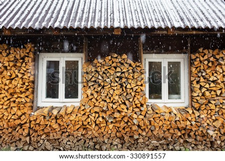 Windows of a traditional country cottage house with firewood logs during snowfall. - stock photo