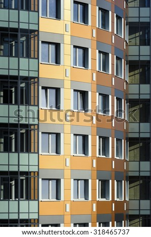 Windows of apartment blocks, residential building in modern architectural style, custom curved orange wall with white and grey construction tile and glazed balconies in green and turquoise shades  - stock photo