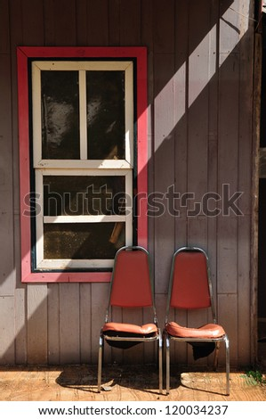 Windows of old, wooden cottage in the countryside with steal chair - stock photo
