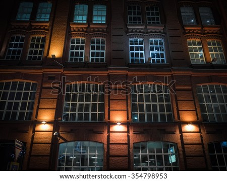 Windows on a brick wall a old fashioned business-building with night illumination - stock photo